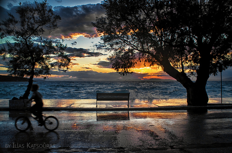 A boy with a bicycle and a sunset with clouds and reflections